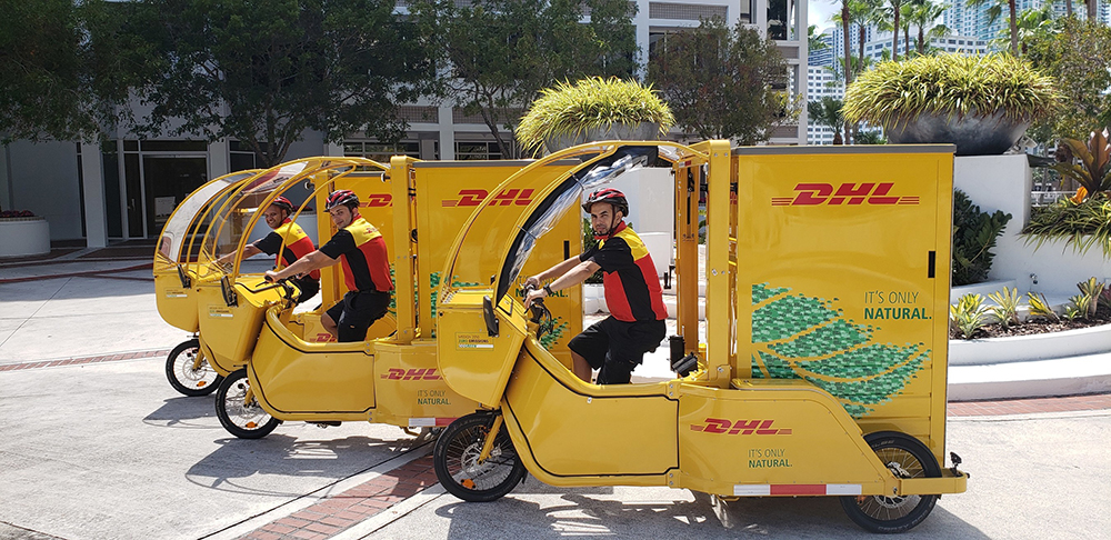 REEF Technology, which turns underutilized commercial spaces such as parking infrastructure into logistics hubs and neighborhood kitchens, teamed up with DHL Express last year to pilot the use of electric-assist cycles for sustainable pickup and delivery in Miami. Image courtesy of PRNewsfoto/DHL