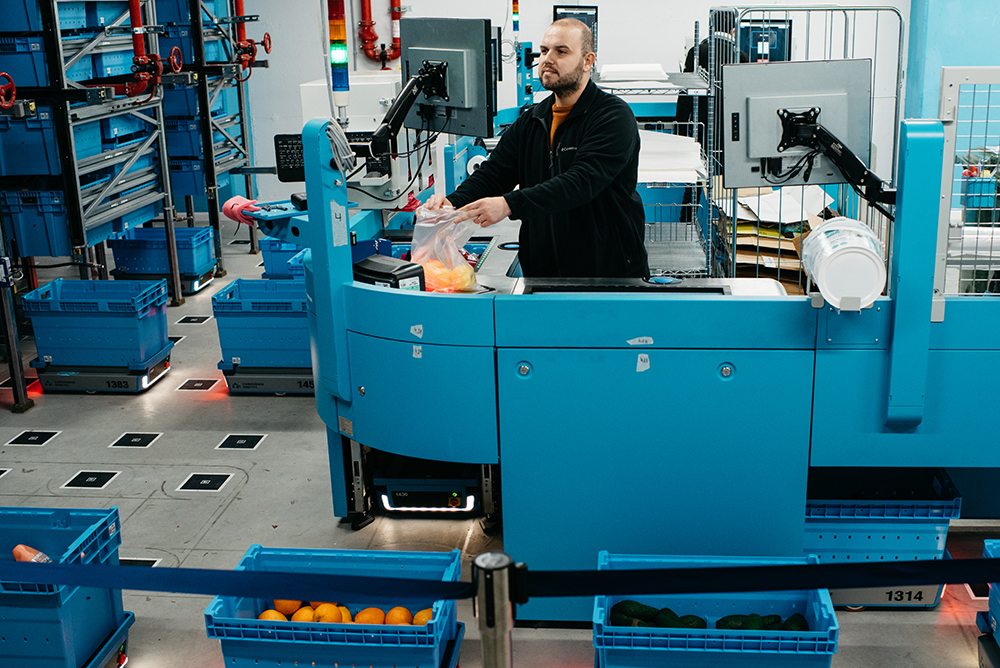 An employee fills a grocery order as robotic totes scurry around in Fabric's 18,000-square-foot underground warehouse in Tel Aviv, Israel, which features three temperature zones. Image courtesy of Fabric